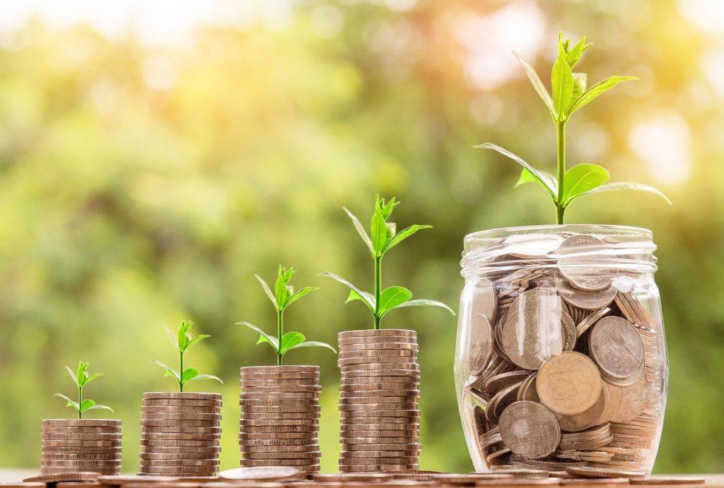 Pile de pièces de monnaies grandissante, finissant dans un pot, représentation d'économies réalisées